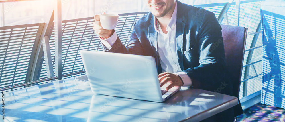 Fototapeta businessman working on computer, drinking coffee and smiling, abstract business banner background with place for text