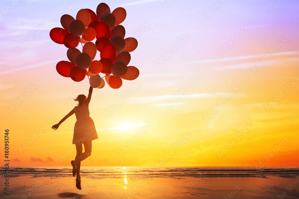 Fototapeta happiness or dream concept, silhouette of happy woman jumping with multicolored balloons at sunset on the beach