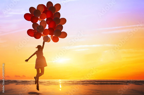 Fototapeta happiness or dream concept, silhouette of happy woman jumping with multicolored balloons at sunset on the beach obraz