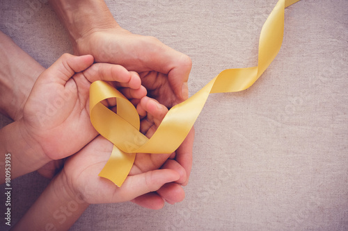adult and child hands holding yellow gold ribbon, Sarcoma Awareness, Bone cancer Fototapet