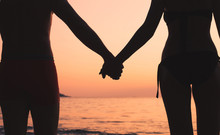 Romantic Travel, Couple On The Beach, Silhouette Of Man And Woman Holding Hands At Sunset