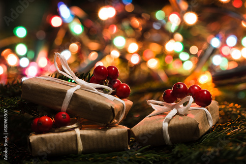 Fotografiet Christmas gift in rustic style and colorful lights blurred in the background