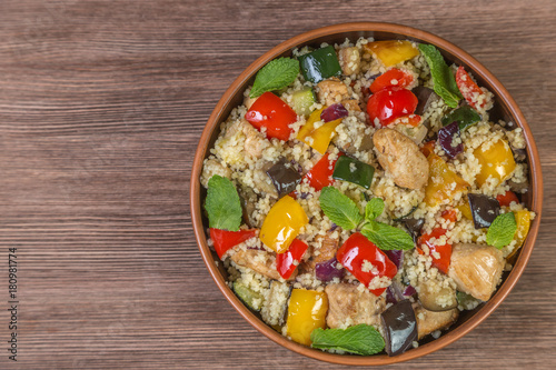 Tabbouleh salad with roasted vegetables, chicken and couscous. Close-up. The view from the top. Copy space.