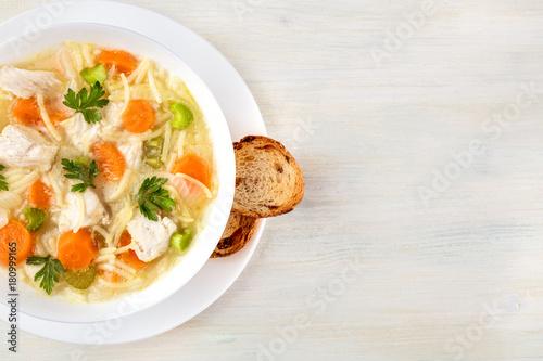 Obraz na płótnie Chicken soup with noodles, overhead photo with copyspace
