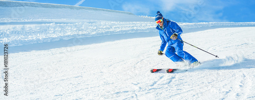 Ingelijste posters Wintersporten Young athlete skiing in alps mountains on sunny day