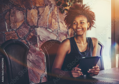 Valokuvatapetti Cheerful young Brazilian female student with curly African hair is sitting at th