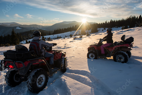 Young couple riders sitting on off-road quad bikes, enjoying beautiful sunset in the the mountains in winter