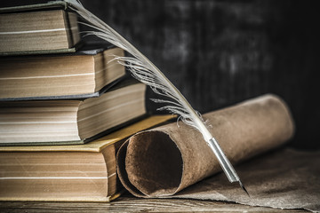 Stary pióro gęsie ze starego papieru przewijania i książek na stole. Pisanie listów. Historyczna atmosfera.