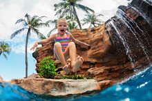 Funny Child Learn To Swim With Fun. Girl Jumping High With Splashes Into Water Pool Under Waterfall. Healthy Lifestyle, Kids Water Sport Activity, Swimming Lesson With Parents On Family Beach Vacation