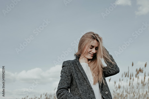 Valokuva  Pretty young and slim woman with long blonde hair posing at camera outdoor on sky background