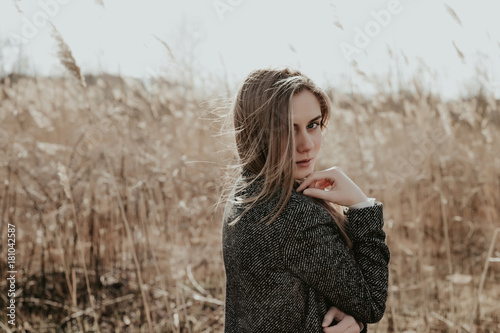 Bonde woman with long hair in wool coat  looking at camera over her shoulder Canvas-taulu