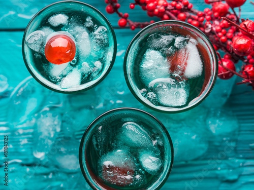 Short alcohol green drinks with cherry and crushed ice. Christmas Saint Patrick day holiday shot