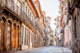 Fototapeta Uliczki - View on the narrow street with beautiful ancient buildings in Porto city, Portugal