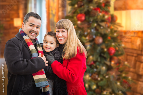 Foto  Young Mixed Race Family Portrait In Front of Christmas Tree Indoors