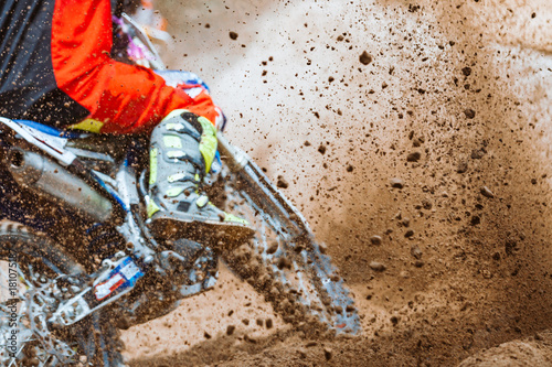 Fotografía  Details of flying debris during an acceleration with mountain bikes race in dirt track in sunshine day time in blurry background