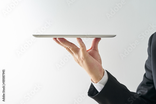 Fotografía  Waiter hand holding an empty digital tablet, Isolated on white background