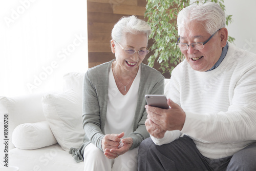 Obraz An old couple is using smartphones as they get along - fototapety do salonu