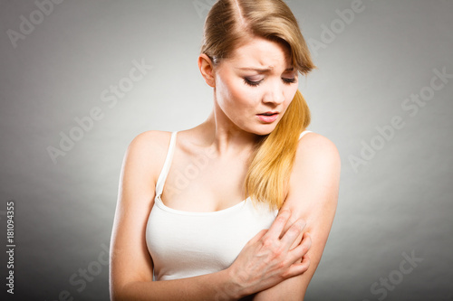 Foto  woman scratching her itchy arm with allergy rash