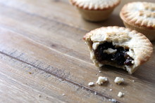 Selection Of Several Mince Pies, Some Broken Open Or Partly Eaten. A Traditional Festive Christmas Dessert Or Pudding.