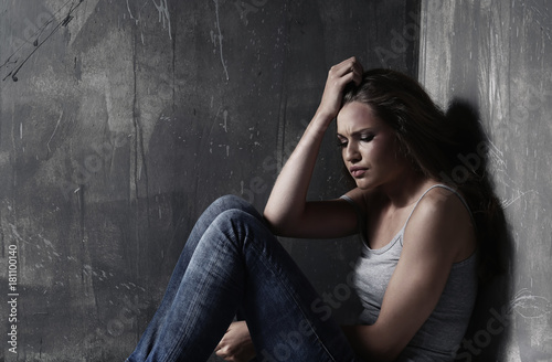 Vászonkép Battered sad woman sitting alone near grey wall