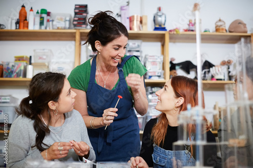 Cheerful mature female engineer standing by colleagues at workshop