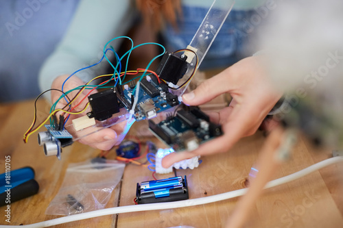 Midsection of young female engineer holding technology at table in workshop