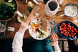 Midsection of woman holding wineglass while having healthy lunch in cottage