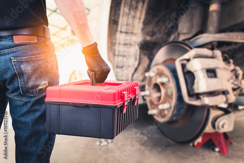 Fotografía  The abstract image of the back of technician hold a toolbox and blurred disc brake is backdrop