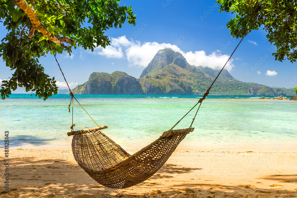 Fototapeta Traditional braided hammock in the shade on a tropical island