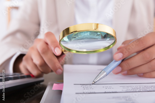 Canvas Print Businesswoman Checking Invoice With Magnifying Glass