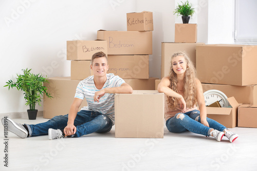 Fototapeta Young couple with moving boxes on floor in room obraz na płótnie
