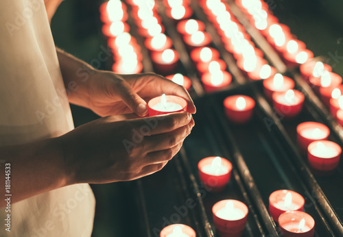 Leinwand Poster Woman holding candle near altar in church.