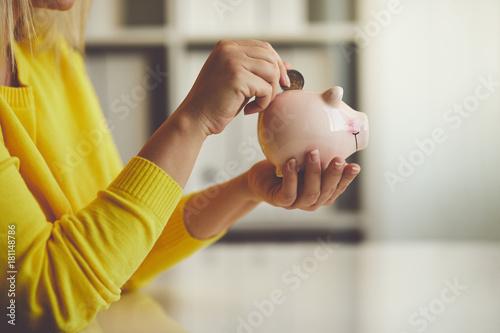 Fotografia  Woman inserts a coin into a piggy bank
