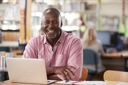 Portrait Of Mature Male Student Using Laptop In Library Wallpaper Mural