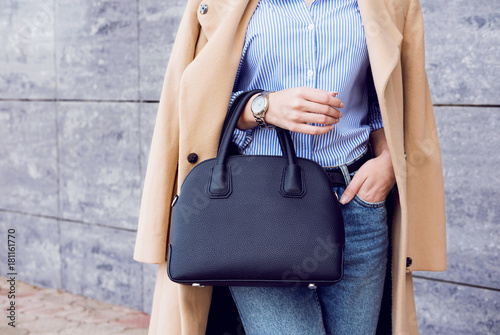 Photo Trendy woman in beige coat and jeans with black big bag