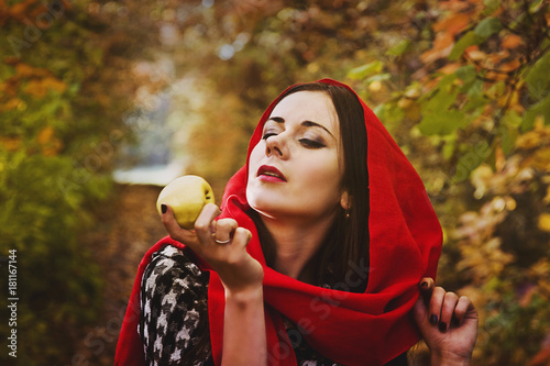 Spoed Foto op Canvas Canada Beautiful girl in a red kerchief holds an apple in an autumn forest