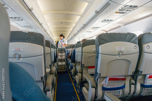 Steward offers food and drinks to economy class passengers on the plane Wallpaper Mural