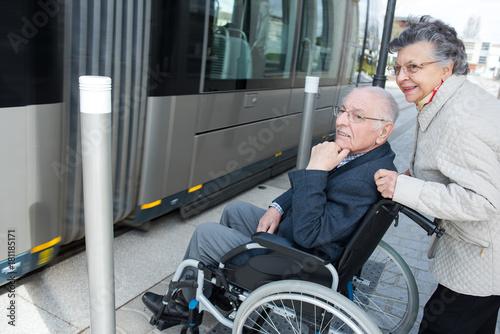 Elderly woman pushing wheelchair bound husband onto tram