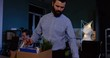 Close up of young caucasian man with a beard packing his stuff inside the box in the office at late evening because he lost his job. Indoors