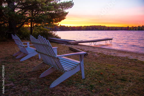 Obraz Summer Vacation At The Lake. Sunset over a lake with a row of Adirondack Chairs, dock and aluminum rowboat. - fototapety do salonu