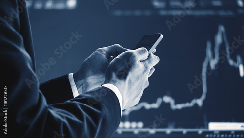 Fototapeta Businessman using mobile smart phone, raising graph background. Business growth, investment and invest in stock exchange market. Online stock market obraz