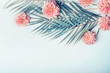 canvas print picture - Creative layout with tropical palm leaves and pastel pink flowers on  light turquoise blue desktop background, top view, place for text, horizontal