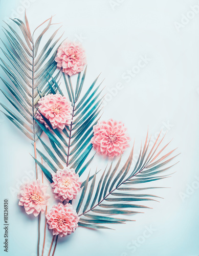 Creative layout with tropical palm leaves and pastel pink flowers on turquoise blue desktop background, top view, place for text, vertical