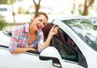 Woman is standing near the convertible car with the keys in hand - concept of buying a used car or a rental car