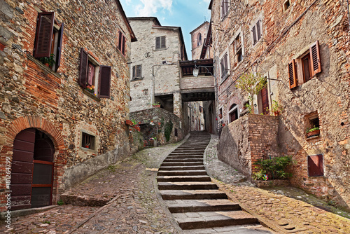 Fototapeten Schmale Gasse Anghiari, Arezzo, Tuscany, Italy: old alley in the medieval village