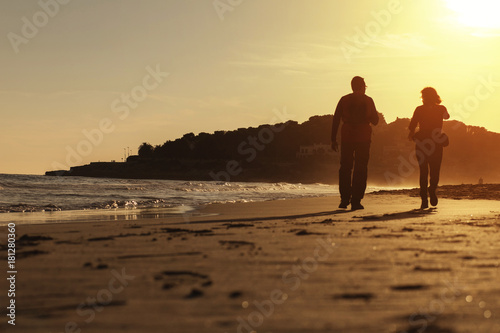 Fotografia, Obraz  Silhouette of couple walking on the beach at sunset