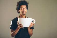 Man Holding Funny Huge And Oversized Cup Of Black Coffee