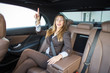 Beautiful businesswoman pointing in limousine where she wants to go