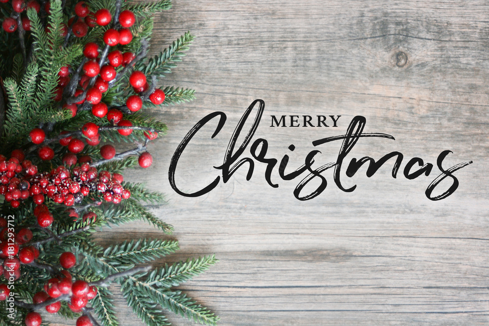 Fototapety, obrazy: Merry Christmas Text with Christmas Evergreen Branches and Berries in Corner Over Rustic Wooden Background