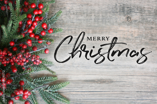 Merry Christmas Text with Christmas Evergreen Branches and Berries in Corner Over Rustic Wooden Background